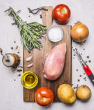 Healthy food for athletes, tomatoes, onions, chicken breast, butter and salt potatoes  wooden rustic background top view close u Royalty Free Stock Image