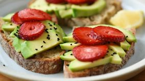 Healthy food - avocado toast with strawberry and seeds. Healthy food. Bread toast with avocado and strawberry on plate, closeup view stock video footage