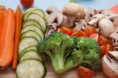 Cut raw vegetables, selective focus on broccoli, closeup. Healthy food background. Cut raw vegetables on wooden board. Chopped and sliced ingredients for salad Royalty Free Stock Images