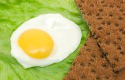 Healthy food background: fried eggs, lettuce, crisp bread Stock Photos