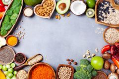 Healthy food background from fruits, vegetables, cereal, nuts and superfood. Dietary and balanced vegetarian eating products. On kitchen table top view royalty free stock images