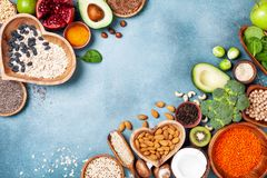 Healthy food background from fruits, vegetables, cereal, nuts and superfood. Dietary and balanced vegetarian eating products. On kitchen table top view royalty free stock image