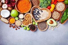 Healthy food background from fruits, vegetables, cereal, nuts and superfood. Dietary and balanced vegetarian eating products. On kitchen table top view stock photos