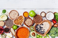 Healthy food background from fruits, vegetables, cereal, nuts and superfood. Dietary and balanced vegetarian eating products. On kitchen table top view stock photography
