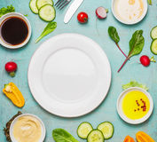 Healthy food background with salad ingredients with various dressing and blank plate, top view. Diet eating. Vegetarian or vegan food concept royalty free stock images