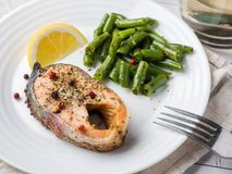 Healthy food. Baked red fish, pink salmon, salmon and green beans with a slice of lemon on a plate. Healthy food. Baked red fish, pink salmon, salmon and green stock image
