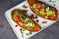 Healthy food - Baked sweet potatoes served with guacamole, feta cheese and pomegranate. Top view stock image