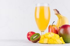Healthy food and beverage - summer fresh cocktail of different tropical fruits with sliced ingredients on soft white wood board. Healthy food and beverage royalty free stock image