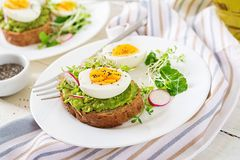 Avocado egg sandwich with whole grain bread on white wooden background. Healthy food. Breakfast. Avocado egg sandwich with whole grain bread on white wooden royalty free stock photo