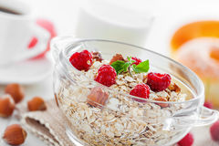 Healthy food breakfast. Delicious healthy food breakfast. Oatmeal  muesli with raspberry and hazelnut on table Stock Photos