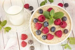 Oatmeal with raspberries.Healthy food for breakfast.Tasty oatmea. Healthy food for breakfast.Oatmeal with raspberries.Tasty oatmeal with berries in bowl on table Royalty Free Stock Images