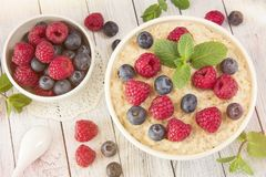 Oatmeal with raspberries.Healthy food for breakfast.Tasty oatmea. Healthy food for breakfast.Oatmeal with raspberries.Tasty oatmeal with berries in bowl on table Stock Images