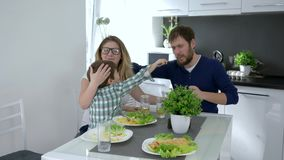 Healthy food, cheerful mom and dad with son eating freshly prepared meal in kitchen. At home stock footage
