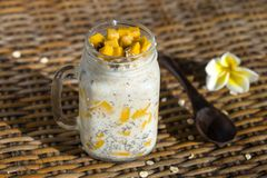Healthy food, chia seed pudding with mango, oat flakes, coconut milk and muesli, vitamin breakfast in glass mug. Morning in Thaila Stock Photography