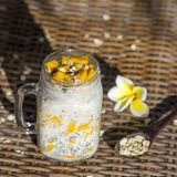 Healthy food, chia seed pudding with mango, oat flakes, coconut milk and muesli, vitamin breakfast in glass mug. Morning in Thaila Stock Photo