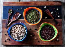 Healthy food - chickpeas, red beans, green peas on old wooden background. Stock Image