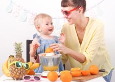 Healthy food for children: Mom and daughter make fresh orange juice. Portrait royalty free stock image