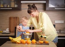 Healthy food for children: Mom and daughter make fresh orange juice. Portrait royalty free stock photos