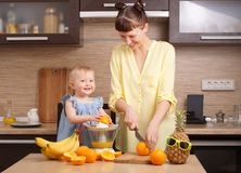 Healthy food for children: Mom and daughter make fresh orange juice. Portrait stock photography