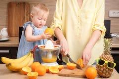 Healthy food for children: Mom and daughter make fresh orange juice. Portrait stock photos