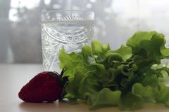 Healthy food, glass and next salad and strawberries. Healthy food, clean water in a glass and next to lie a green salad and strawberries royalty free stock images