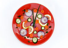 Healthy food clock. Various vegetable on red plate isolated over white Stock Photos
