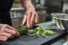 Healthy food. Close up of male hands with beautiful tattoos peeling cucumber for salad while standing in a restaurant stock image