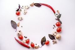 Creative layout made of seasonal summer vegetables. Healthy food composition. Frame made of cherry tomatoes, champignons,  basil leaves, garlic, chilly pepper on stock images