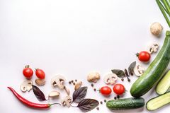 Healthy seasonal food composition with copy space. Healthy food composition. Frame made of cherry tomatoes, champignons, cucumber, basil leaves, garlic, chilly stock photography