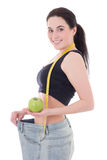 Healthy food concept - beautiful slim woman in big jeans with ap Royalty Free Stock Image
