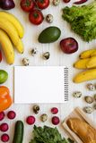 Healthy food concept. Composition of raw healthy food with blank notepad on a white wooden table. Flat lay. Top view. From above stock images