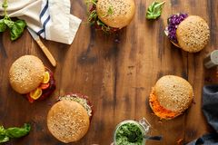 Healthy food concept. Frame of set vegetarian burgers. Frame of set vegetarian burgers with beet cutlets and prunes, tomato; cabbage, cucumber, alfalfa, pea Stock Photos
