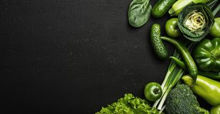 Healthy food concept with fresh, green vegetables on black stone table. Top view with copy space royalty free stock images