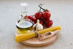 Healthy food. Concept. Fresh, tasty tomatoes, olive oil, pasta, pink salt, garlic on wooden plate royalty free stock photo