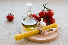 Healthy food. Concept. Fresh, tasty tomatoes, olive oil, pasta, pink salt, garlic on wooden plate stock photo