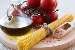 Healthy food. Concept. Fresh, tasty tomatoes, olive oil, pasta, pink salt, garlic on wooden plate royalty free stock photos