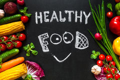 Healthy food concept with fresh vegetables for cooking.Title `Healthy food` with smile is written by chalk on the background. Photo of a table top full of fresh Stock Photos