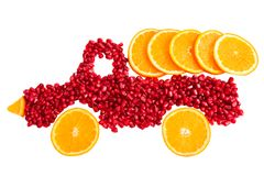 Healthy food concept with fruits. Seeds of pomegranate and slices of orange are as shape of lorry with cargo of orange royalty free stock photography