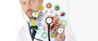 Healthy food concept, Hand of nutritionist doctor pointing fruits. Icon with stethoscope Stock Photography