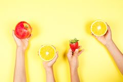 Healthy food concept. Many kids hands with fuits on yellow background. Top view stock photos