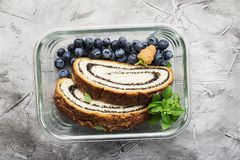Healthy food in containers: breakfast with poppy seed roll and fresh berries in a glass lunch box to go. Top view. Healthy food in containers: breakfast with stock photography