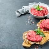 Homemade raw organic minced beef meat and burger cutlet. Healthy food, cooking concept. Homemade raw organic minced beef meat and burger cutlet on a grunge black royalty free stock image