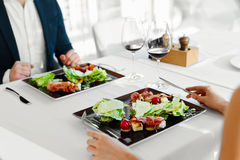 Healthy Food. Couple Eating Caesar Salad For Meal In Restaurant. Stock Photos