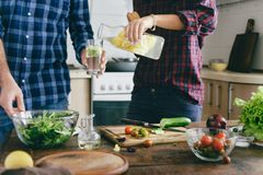 Healthy food. Couple preparing summer salad home kitchen stock photography