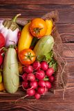 Fresh Vegetables in wooden box on brown wooden background. Healthy food delivery background. Lunch box with colorful tomatoes, zucchini Royalty Free Stock Image
