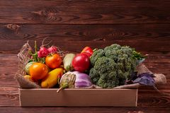Fresh Vegetables in wooden box on brown wooden background. Healthy food delivery background. Lunch box with colorful tomatoes, zucchini Royalty Free Stock Photos
