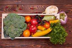 Fresh Vegetables in wooden box on brown wooden background. Healthy food delivery background. Lunch box with colorful tomatoes, zucchini Royalty Free Stock Photography