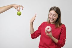 Healthy food and diet concept. Beautiful young woman choosing between fruits and sweets. She prefer a pink donut instead of green apple royalty free stock images