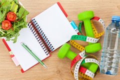 Healthy food, dumbells, tape measure and notepad for copy space Royalty Free Stock Image