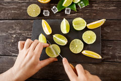 Healthy food and eating. woman cutting the lemons on black board Royalty Free Stock Images